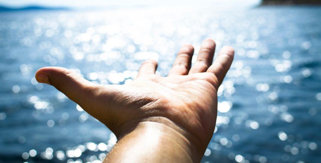 Mão demonstrando o experimento prático proposto